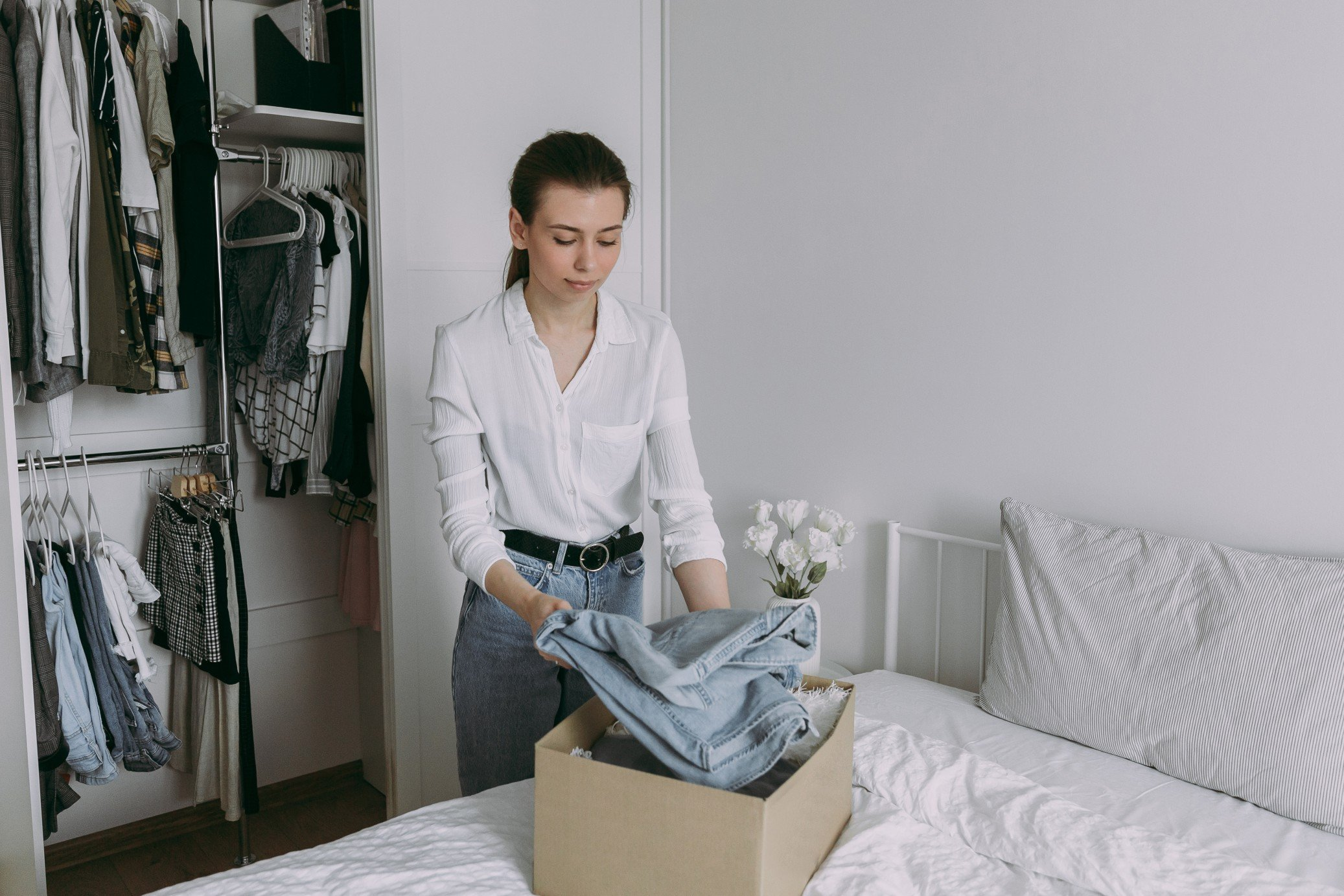 a-young-girl-near-the-wardrobe-sorts-clothes-and-donates-clothes-to-charity-the-girl-takes-things-for_t20_rLeL8J